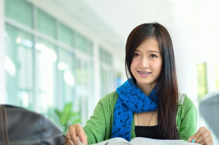beautiful asian girl is reading and smile