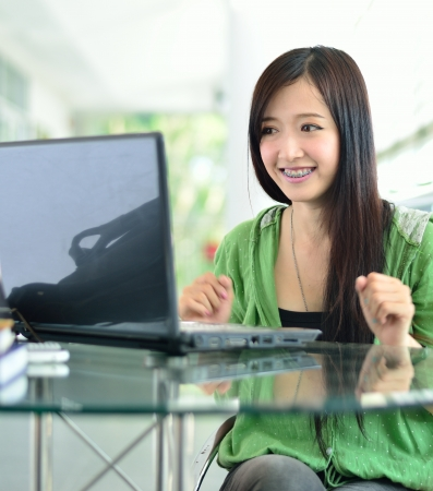 Beautiful young student have good news on the computer screen Stock Photo