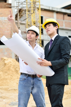 asian architect: Two engineers are working on a construction area
