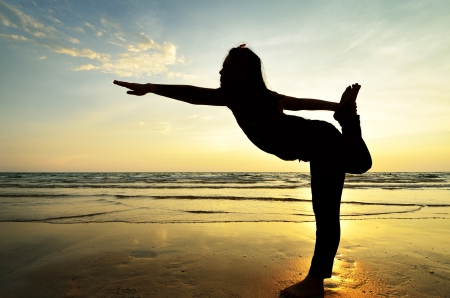 silhouette Asian woman practicing yoga at the beach Stock Photo
