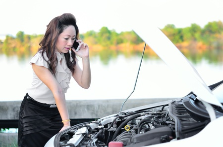 communication breakdown: Female driver on the phone and car breakdown