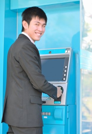 Asian business man using Automatic Telling Machine photo