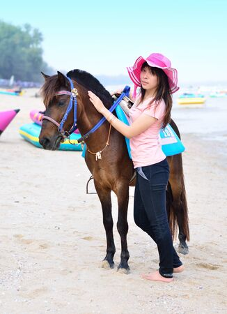 beautiful asian woman with brown horse on beach photo