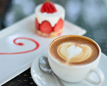 Close up coffee latte art and strawberry cake