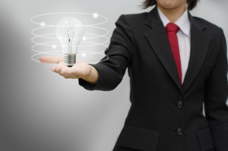 technology metaphor: Business woman holding idea lamp