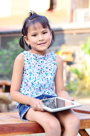 Asian young girl using computer tablet photo