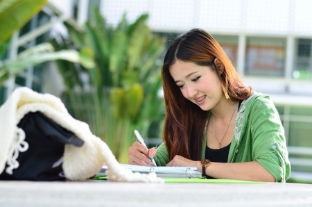 Beautiful young asian student is reading and writing homework Stockfoto