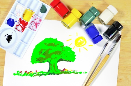 Watercolor brushes, art paper board on wood background photo