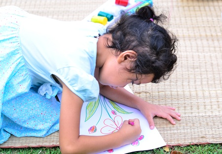 Going back to school   Colse up girl drawing and painting over green grass background