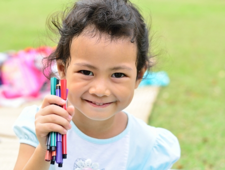 Going back to school   Close up little girl holding color pens photo