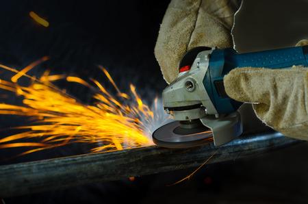 Close up iron worker cutting metal Foto de archivo