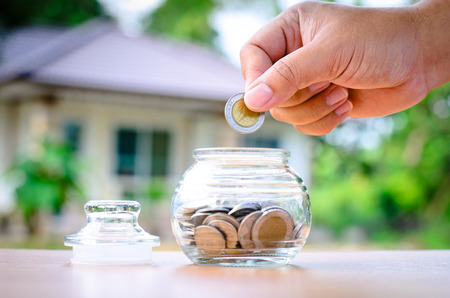 Male hand putting money coins with home, Saving for buy home concept Standard-Bild