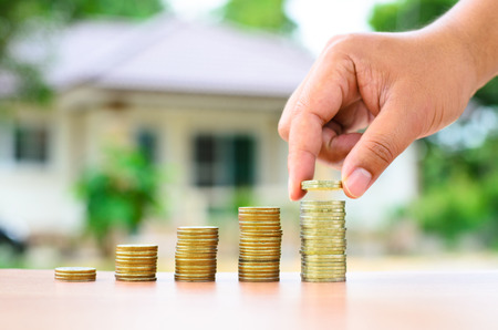 property: Male hand putting money coins stack like growing graph with home, Saving for buy home concept
