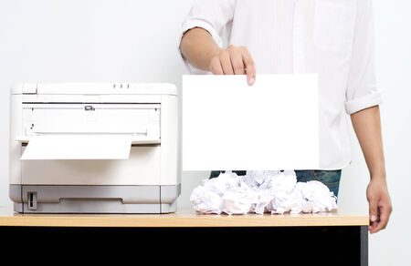 Businessman showing blank paper near color printer on table in office