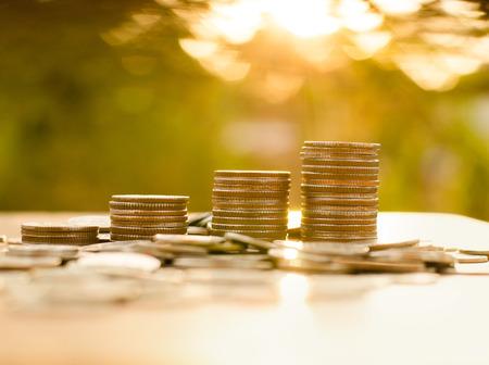 apilar: Pila de monedas de dinero gráfico cada vez mayor con la luz del sol