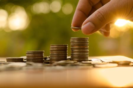 Mężczyzna strony wprowadzenie monety stos rośnie wykres z promieni słonecznych Zdjęcie Seryjne