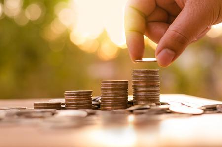 prosperidad: Hombre mano poniendo pila de monedas gr�fico cada vez mayor con la luz del sol