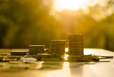 prosperidad: Pila de monedas de dinero gr�fico cada vez mayor con la luz del sol