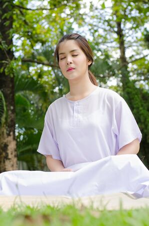 happier: meditation woman nature,Buddhist thai woman happy with white clothing sitting for concentration on green grass background.