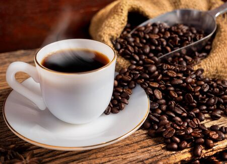 cup of coffee: Hot coffee with cup and coffee bean bag on old wood background vintage style