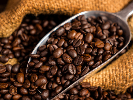 Close up coffee bean with bag and spoon on wood background