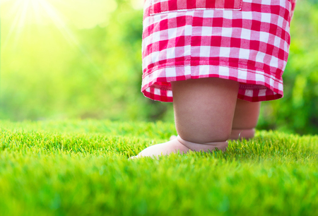 Baby standing on green grass with sunlight background,Startup concept Stockfoto