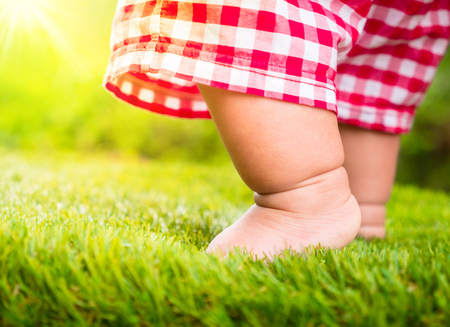 Baby start walking first time on green grass with sunlight background,Startup concept