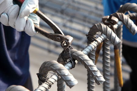 hands of builder worker use pincers and wires for knitting metal Standard-Bild