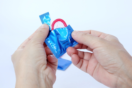 Woman holding condom in hand,Hand holding a condom in package,isolated on white background  photo