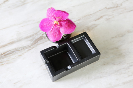 quiting: Empty black ash tray on a stone background
