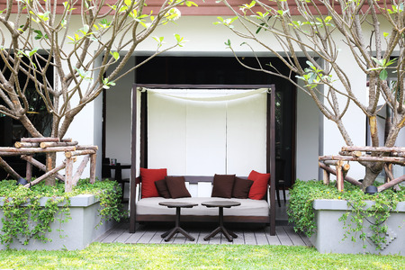 Outdoor patio seating area with nice Fabric sofa at sunset  Standard-Bild