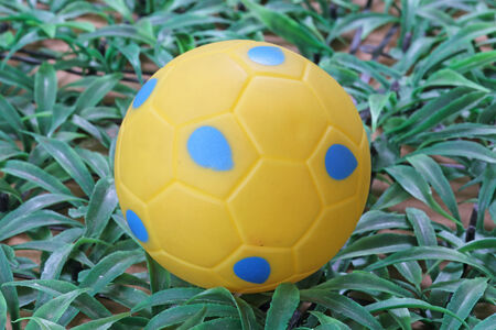 Yellow  and blue  soccer ball on artificial grass photo