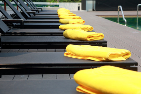 Yellow towel  on black sunbeds by the resort pool