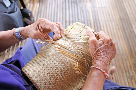 handcrafted: manually weaving bamboo basket in Thailand Stock Photo