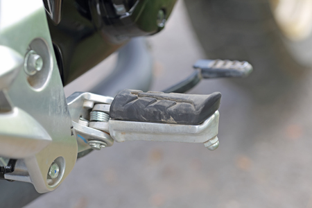Detail with the foot-rest of a motorcycle.  Stock Photo