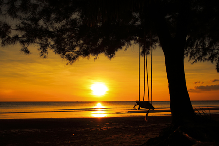 Wooden swing hanging on  tree with a sunset beach,Beautiful sea tropical landscape. photo