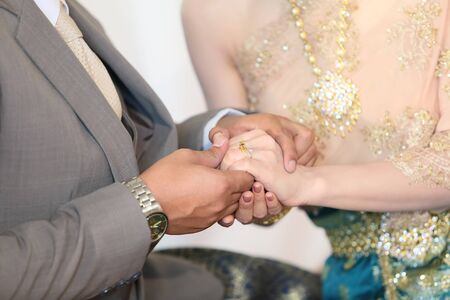 Thai groom putting a wedding ring photo