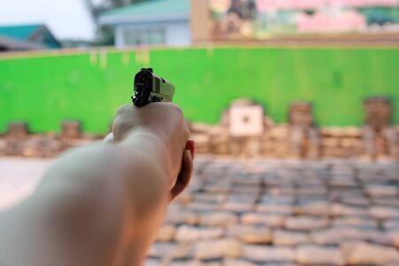 adentro y afuera: una persona no identificable dispara una pistola de alta potencia. poca profundidad de campo foto por lo que el fondo fuera de foco y el foco est� en la pistola Foto de archivo