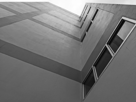 tall building: Abstract modern architecture. Perspective of tall building with dark windows and walls.