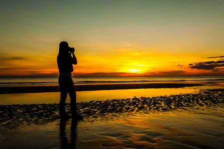 Silhouette woman photographer walking on beach with hand holding camera at sunrise.