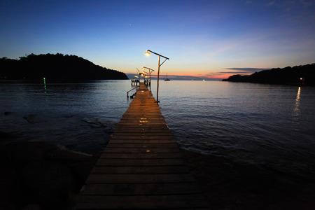 Long wood bridge with evening sea Stock Photo