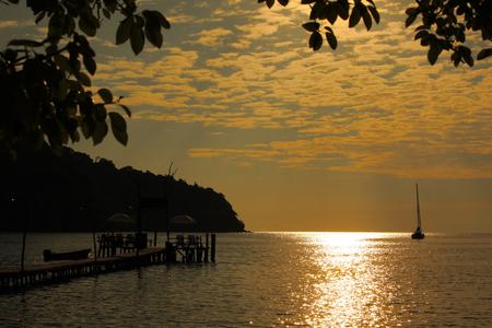 Boat sailing with orange sunset background Standard-Bild