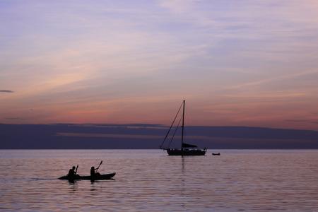 Family Sea Kayaking at Sunset Stock Photo