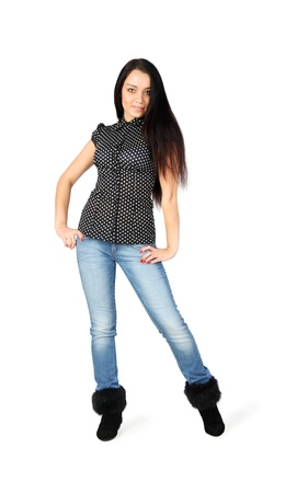 beautiful girl wearing jeans and boots with fur stands isolated on white background photo
