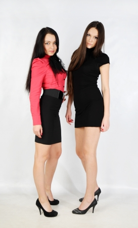 two beautiful young girls stand and look at camera in white studio; full body photo
