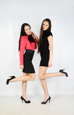 sisters sexy: two beautiful young girls stand and hold hands in white studio; full body Stock Photo