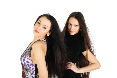 two beautiful brunette girls look at camera inside white studio photo