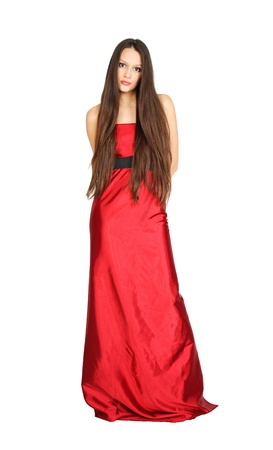 Cute girl wing long hair wearing long red dress stands isolated on white background photo
