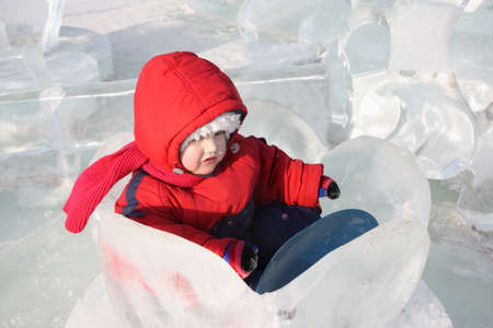 nenuphar: Little girl wearing warm jumpsuit sits in ice nenuphar at winter outdoor