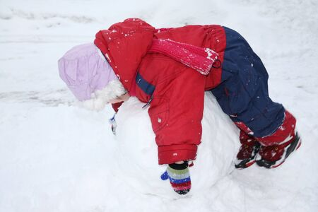 Little girl wearing warm jumpsuit lies on big snowball; child rolls snowball photo